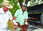 Cooking brisket and ribs, Curtis Warman, left, and Chris Allman wrap up their cooked meat to keep it warm. The two said cooking great barbecue requires time and patience.
