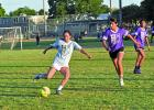 "Teresa Neri, soccer player for ""The Justice League"" slams the ball away from ""The Texicans"" defenders Anahi Arias, Nahomi Arias and Enrique Ramirez during a soccer game on Wednesday, July 13. — Standard- Radio Post/ Scott Allen"